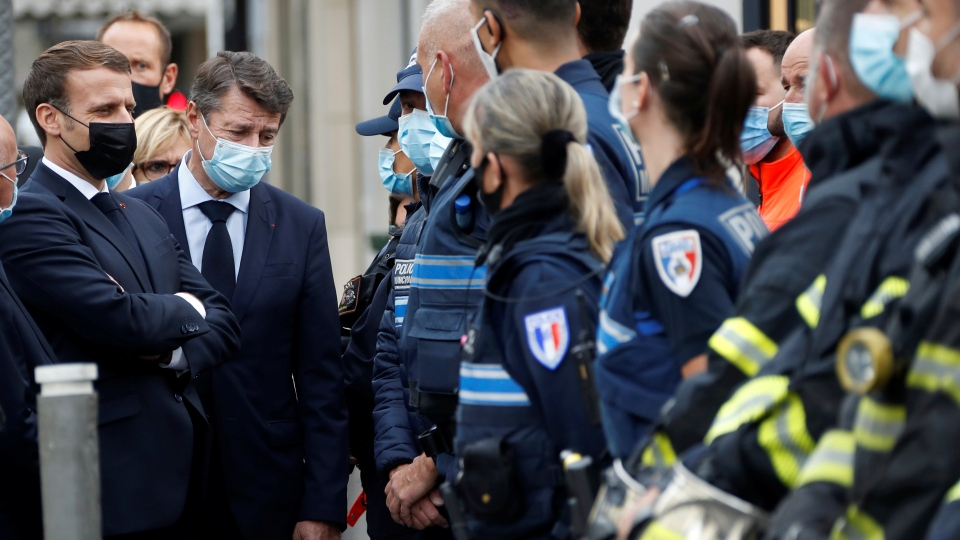 French President Emmanuel Macron, left, and Nice mayor Christian Estrosi , second left, meet police officers and rescue workers after a knife attack at Notre Dame church in Nice, southern France, Thursday, Oct. 29, 2020. (Eric Gaillard/Pool via AP)