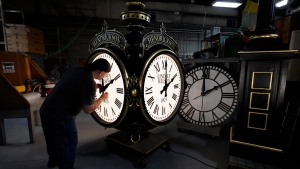 Dan LaMoore adjusts the hands on a Seth Thomas Post Clock at Electric Time Company, Friday, Oct. 23, 2020, in Medfield, Mass. Daylight saving time ends at 2 a.m. local time Sunday, Nov. 1, 2020, when clocks are set back one hour. (AP Photo/Elise Amendola)
