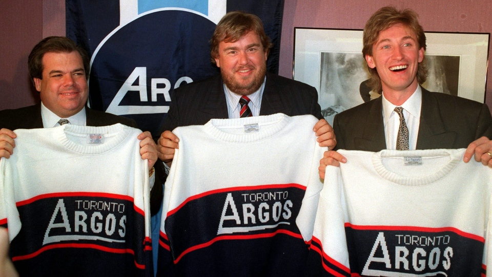 Los Angeles Kings owner Bruce McNall (left to right), comedian John Candy and hockey superstar Wayne Gretzky show off their new Argonaut jerseys in Toronto Feb. 25, 1991 after it was announced they purchased the Canadian Football League team. (CP PHOTO/Blaise Edwards)