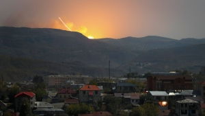 Explosions are seen behind the mountains during a military conflict outside Stepanakert, the separatist region of Nagorno-Karabakh, Friday, Oct. 30, 2020. The Azerbaijani army has closed in on a key town in the separatist territory of Nagorno-Karabakh following more than a month of intense fighting. (AP Photo)