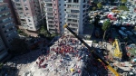Photo taken with a drone shows rescue workers trying to save residents trapped in debris of a collapsed building, in Izmir, Turkey, Saturday, Oct. 31, 2020. Rescue teams on Saturday ploughed through concrete blocs and debris of eight collapsed buildings in search of survivors of a powerful earthquake that struck Turkey's Aegean coast and north of the Greek island of Samos, leaving unknown numbers of dead and injured.(IHA via AP)