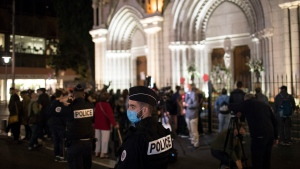 A policeman stands guard in front of the Notre Dame church in Nice, France, Friday, Oct. 30, 2020. A new suspect is in custody in the investigation into a gruesome attack by a Tunisian man who killed three people in a French church. France heightened its security alert amid religious and geopolitical tensions around cartoons mocking the Muslim prophet. (AP Photo/Daniel Cole)