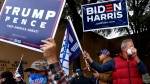 Biden-Harris and Trump-Pence supporters stand together at Vera Minter Park in Abilene, Texas as they await the arrival of the Biden-Harris campaign bus Wednesday Oct. 28, 2020. (Ronald W. Erdrich/The Abilene Reporter-News via AP)
