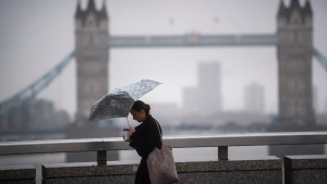 A morning commuter crosses the River Thames on London Bridge in central London, backdropped by Tower Bridge, as storm weather warnings are issued Wednesday Oct. 21, 2020. A storm is predicted to bring gale force winds and heavy rain to southern parts of the UK. (Victoria Jones/PA via AP)