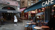 A woman walks by cafes and restaurants in the center of Lyon, central France, Friday, Oct. 2, 2020. (AP Photo/Laurent Cipriani)