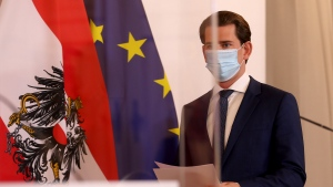 Austrian Chancellor Sebastian Kurz wears a face mask as he arrives behind plexiglass shields for a press conference at the federal chancellery in Vienna, Austria, Saturday, Oct. 31, 2020. The Austrian government has moved to restrict freedom of movement for people, in an effort to slow the onset of the COVID-19 coronavirus. (AP Photo/Ronald Zak)