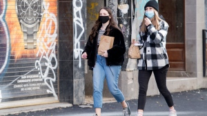 People wear face masks as they walk along a street in Montreal, Saturday, October 31, 2020, as the COVID-19 pandemic continues in Canada and around the world. THE CANADIAN PRESS/Graham Hughes