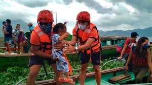 In this photo provided by the Philippine Coast Guard, members of the Philippine Coast Guard carry a child as they are evacuated to safer ground in Camarines Sur province, eastern Philippines on Saturday Oct. 31, 2020 as they prepare for typhoon Goni. Families living near coastal towns have started moving to evacuation centers as the strong typhoon approaches the country. (Philippine Coast Guard via AP)