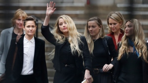 American actress Amber Heard, former wife of actor Johnny Depp, waves as she leaves the High Court in London, Tuesday, July 28, 2020. Hollywood actor Johnny Depp is suing News Group Newspapers over a story about his former wife Amber Heard, published in The Sun in 2018 which branded him a 'wife beater', a claim he denies. (AP Photo/Alastair Grant)