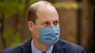 "FILE - In this Oct. 20, 2020, file photo, wearing a face covering to curb the spread of coronavirus Britain's Prince William meets pharmacist Joyce Duah as he and his wife Kate the Duchess of Cambridge visit St. Bartholomew's Hospital in London, to mark the launch of the nationwide ""Hold Still"" community photography project. Prince William tested positive for the coronavirus, apparently around the same time as his father Prince Charles earlier this year, BBC reported. (AP Photo/Matt Dunham, Pool, File)"