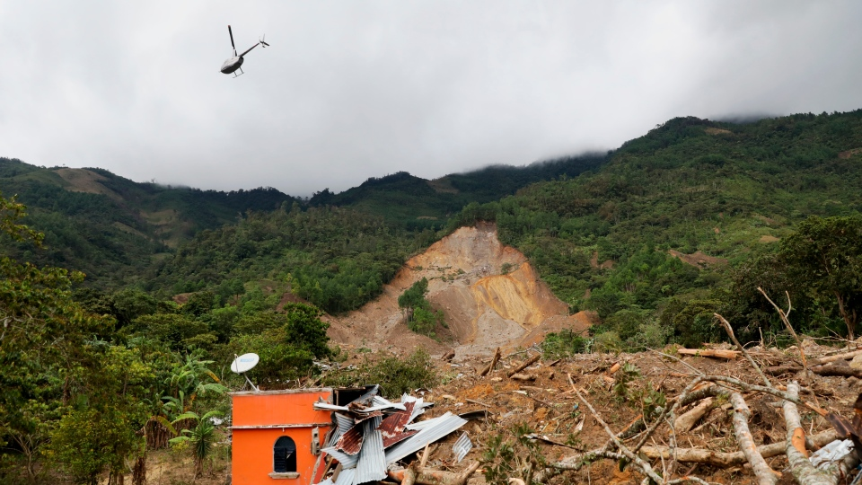 A helicopter flies over the massive, rain-fueled landslide in the village of Queja, in Guatemala, Saturday, Nov. 7, 2020, in the aftermath of Tropical Storm Eta. (Esteban Biba/Pool Photo via AP)