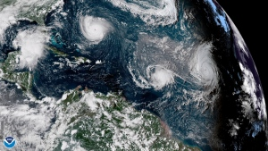 FILE - This enhanced satellite image made available by NOAA shows Tropical Storm Florence, upper left, in the Atlantic Ocean on Tuesday, Sept. 11, 2018 at 3:30 p.m. EDT. At center is Tropical Storm Isaac and at right is Hurricane Helene. According to a study released on Wednesday, Nov. 11, 2020, hurricanes are keeping their staying power longer once they make landfall, spreading more inland destruction. (NOAA via AP)