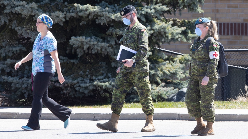 A staff member escorts members of the Canadian Armed Forces in to a long term care home, in Pickering, Ont. on Saturday, April 25, 2020. The Canadian Armed Forces says minor problems remain in some Ontario long-term care homes they were deployed to earlier in the COVID-19 pandemic. THE CANADIAN PRESS/Chris Young