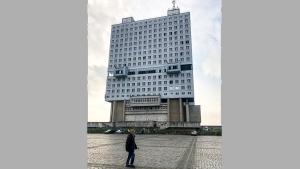 A man walks past the never-occupied building in Kaliningrad, Russia, Thursday, Oct. 29, 2020. The hulking never-occupied building sardonically likened to a robot's head that has loomed over the city of Kaliningrad for decades is to be demolished next year, the region's governor says. The 21-story House of Soviets was left unfinished when funding ran out in 1985 amid the Soviet Union's economic struggles and later was assessed to be structurally unsound. (AP Photo/James Heintz)
