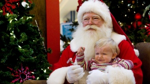 Seventeen-month-old child reacts as she sits with a Santa Claus for a photo at a mall in Toronto on Friday December 10, 2010. THE CANADIAN PRESS/Chris Young