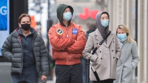 People wear face masks as they wait to enter a store in Montreal, Saturday, November 14, 2020, as the COVID-19 pandemic continues in Canada and around the world. THE CANADIAN PRESS/Graham Hughes