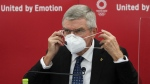 Thomas Bach, International Olympic Committee (IOC) President, puts on his mask before speaking during the joint press conference between IOC and Tokyo Organizing Committee of the Olympic and Paralympic Games (Tokyo 2020) in Tokyo, Japan, Nov. 16, 2020. (Du Xiaoyi/Pool Photo via AP)