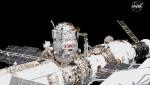 This photo provided by NASA shows Russian astronauts Commander Sergey Ryzhikov, left in red stripes, and Sergey Kud-Sverchkov, back left, on a spacewalk outside of the International Space Station on Wednesday, Nov. 18, 2020, as they prepare for next year's arrival of a long-delayed lab. (NASA via AP)