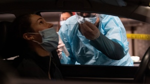 A nurse demonstrates testing at a drive-thru Covid-19 testing centre at the National Arts Centre Wednesday November 18, 2020 in Ottawa. THE CANADIAN PRESS/Adrian Wyld