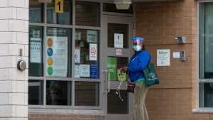 A woman waits to enter Glamorgan Junior Public School in Toronto, Tuesday, Nov. 3, 2020. The school is experiencing an outbreak of COVID-19. THE CANADIAN PRESS/Frank Gunn