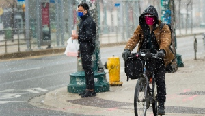 A man cycles in a snow with a mask on in downtown Toronto on Thursday, April 16, 2020. THE CANADIAN PRESS/Nathan Denette