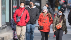 People wear face masks as they walk along a street in Montreal, Saturday, Nov. 21, 2020, as the COVID-19 pandemic continues in Canada and around the world.THE CANADIAN PRESS/Graham Hughe