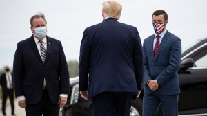 FILE - In this May 21, 2020, file photo, President Donald Trump is greeted by Kurt Heise, left, Supervisor of Plymouth Township, Mich., and Speaker Lee Chatfield, of the Michigan House of Representatives after stepping off Air Force One as he arrives at Detroit Metro Airport in Detroit. (AP Photo/Alex Brandon, File)