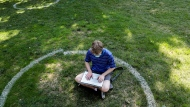 Logan Armstrong, a Cincinnati junior, works while sitting inside a painted circle on the lawn of the Oval during the first day of fall classes on Tuesday, Aug. 25, 2020 at Ohio State University in Columbus, Ohio. (Joshua A. Bickel/The Columbus Dispatch via AP)