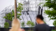 "People look at a collapsed stage at Downsview Park in Toronto on June 16, 2012. The members of Radiohead say they are ""appalled"" that charges stemming from a fatal concert stage collapse in Toronto in 2012 were stayed. On Tuesday, a judge ruled the justice system had failed by allowing the case to take far too long to come to trial. THE CANADIAN PRESS/Nathan Denette"