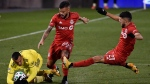 Nashville SC's Randall Leal, left, falls next to Toronto FC's Auro Jr., center, and Jonathan Osorio during the second half of an MLS soccer playoff match Tuesday, Nov. 24, 2020, in East Hartford, Conn. (AP Photo/Jessica Hill)