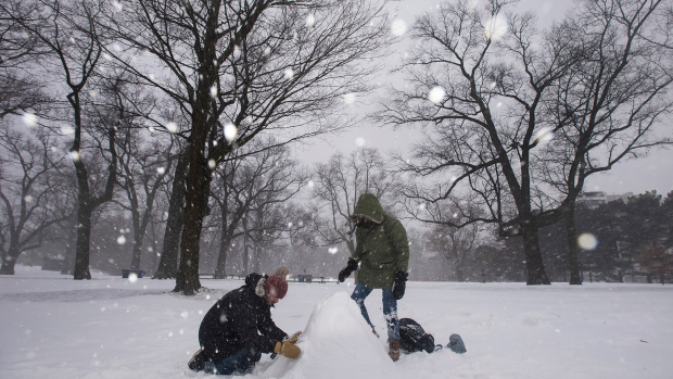 Rafael Ravara, left, and Alano Silva, take advantage of the winter storm to build their first snowman at High Park in Toronto on Tuesday, February 12, 2019. THE CANADIAN PRESS/ Tijana Martin