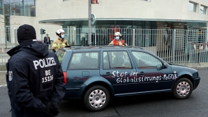 A car stands in front of the chancellery after it crashed into the front gate of the building housing German Chancellor Angela Merkel's offices in Berlin, Germany, Wednesday, Nov. 25, 2020. Slogan reads 'stop the globalization policies'. (AP Photo/Michael Sohn)