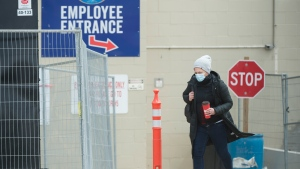 An employee wearing a masks leaves work at the Maple Lodge Farms poultry processing plant during the COVID-19 pandemic in Brampton, Ont., on Friday, May 8, 2020. THE CANADIAN PRESS/Nathan Denette