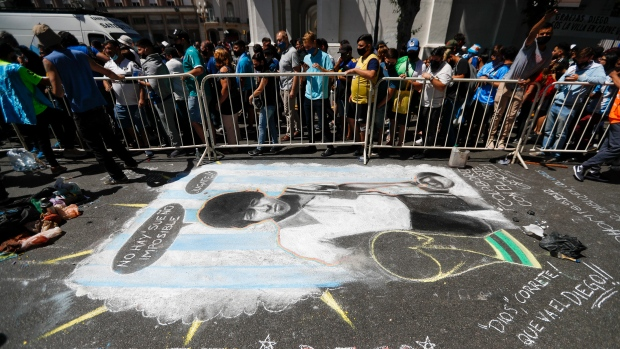 Mourners line up to pay their final respects to Diego Maradona, alongside a chalk drawing of Maradona, outside the presidential palace in Buenos Aires, Argentina, Thursday, Nov. 26, 2020. The Argentine soccer great who was among the best players ever and who led his country to the 1986 World Cup title died from a heart attack at his home Wednesday, at the age of 60. (AP Photo/Natacha Pisarenko)