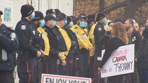 Toronto Police officers block the entrance to Adamson Barbecue in Etobicoke Thursday morning as protesters rally against COVID-19 lockdown rules.