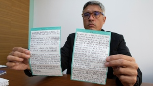 Jesus Loreto, an attorney representing Tomeu Vadell, one of six U.S. oil executives jailed for three years in Venezuela, shows a letter written by Vadell, in Caracas, Venezuela, Wednesday, Nov. 25, 2020. (AP Photo/Ariana Cubillos)
