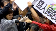 """In this image made from video, Taiwanese Premier Su Tseng-chang holds a microphone as opposition party lawmakers from the Nationalist party (KMT) block his attempt to speak during a parliament session in Taipei, Taiwan, Friday, Nov. 27, 2020. Taiwan's lawmakers got into a fist fight and threw pig guts at each other Friday over a soon-to-be enacted policy that would allow imports of U.S. pork and beef. The banner at right reads: """"Democratic Progressive Party feeds people with ractopamine pork."""" (FTV via AP)"""