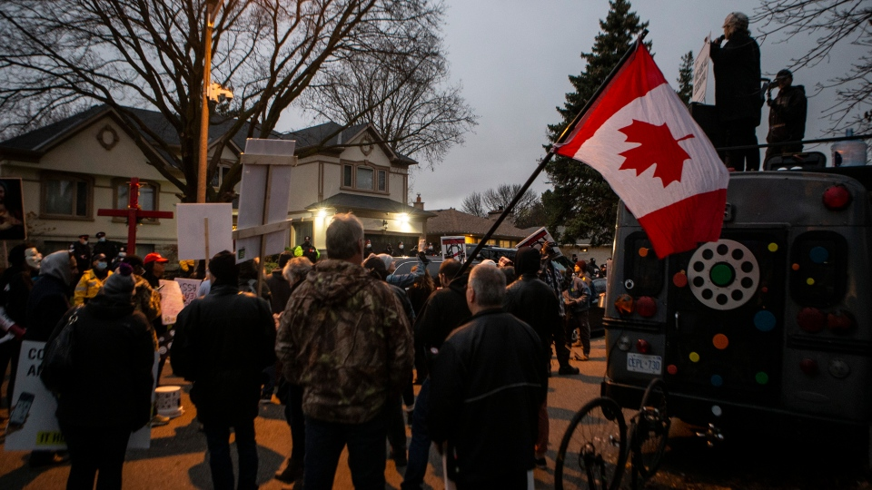 Protesters gather outside of Ontario Premier Doug Ford's house following the arrest of Adam Skelly in Toronto, Thursday, Nov. 26, 2020. Skelly owns a BBQ restaurant which opened in defiance of COVID restrictions. THE CANADIAN PRESS/Chris Young