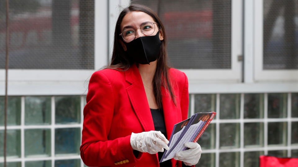 First-term U.S. Rep. Alexandria Ocasio-Cortez, D, New York, hands out leaflets explaining how to vote early or by absentee ballot to passersby at the Parkchester subway station in the Bronx borough of New York, Monday, June 15, 2020, in New York. (AP Photo/Kathy Willens)