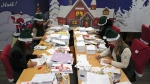 "Postal workers who call themselves ""Elves"" open envelopes addressed to ""Pere Noel"" - Father Christmas in French - decorated with love hearts, stickers and glitter, in Libourne, southwest France, Monday, Nov. 23, 2020. Letters pouring by the tens of thousands into Santa's mailbox offer a glimpse into the worries and hopes of children awaiting a pandemic-hit Christmas. (AP Photo/Francois Mori)"