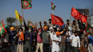 Protesting farmers shout slogans near a barricade on a major highway, refusing to move ahead unless they're allowed to proceed to their place of choice to protest, at the Delhi-Haryana state border, India, Saturday, Nov. 28, 2020. Thousands of farmers in and around the Indian capital on Saturday pressed on with their protest against agricultural legislation they said could devastate crop prices, while the government sought talks with their leaders. (AP Photo/Altaf Qadri)