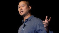 FILE - In this Sept. 30, 2013, file photo, Tony Hsieh speaks during a Grand Rapids Economic Club luncheon in Grand Rapids, Mich. Hsieh, retired CEO of Las Vegas-based online shoe retailer Zappos.com, has died. Hsieh was with family when he died Friday, Nov. 27, 2020, according to a statement from DTP Companies, which he founded. (Cory Morse/The Grand Rapids Press via AP, File)