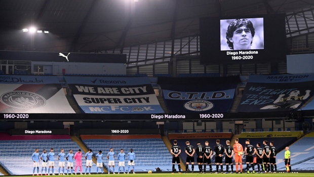 Players observe a minute of silence in memory of former Argentina player and manager Diego Maradona who died from a heart attack on Wednesday, prior to the start of the English Premier League soccer match between Manchester City and Burnley at the Etihad stadium in Manchester, England, Saturday, Nov. 28, 2020. (Laurence Griffiths/Pool via AP)