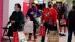 Black Friday shoppers wearing face masks wait in line to enter a store at the Glendale Galleria in Glendale, Calif., Friday, Nov. 27, 2020. (AP Photo/Ringo H.W. Chiu)