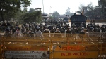 Indian police in riot gear stand behind barricades as protesting farmers block a major highway, refusing to move ahead unless they're allowed to proceed to their place of choice to protest, at the Delhi-Haryana state border, India, Saturday, Nov. 28, 2020. Thousands of farmers in and around the Indian capital on Saturday pressed on with their protest against agricultural legislation they said could devastate crop prices, while the government sought talks with their leaders. (AP Photo/Altaf Qadri)