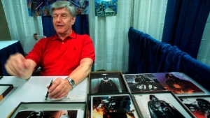 "In this file photo dated Friday, May 7, 1999, Dave Prowse, the original Darth Vader from the ""Star Wars Trilogy,"" poses during the New York Comic and Fantasy Creators Convention.  The British actor, Prowse who played Darth Vader in the original Star Wars trilogy, has died aged 85 on Saturday, according to an announcement by his agent Sunday Nov. 29, 2020. (AP Photo/Lynsey Addario, FILE)"