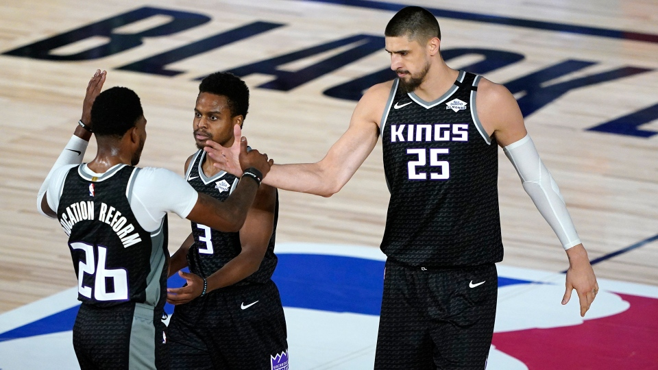 Sacramento Kings' Kent Bazemore (26), Yogi Ferrell (3) and Alex Len (25) celebrate after defeating the New Orleans Pelicans 140-125 during an NBA basketball game Thursday, Aug. 6, 2020 in Lake Buena Vista, Fla. (AP Photo/Ashley Landis, Pool)