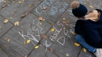 A student chalks graffiti on a sidewalk in front of New York's City Hall during a protest by parents and students opposing the closing of schools, Thursday, Nov. 19, 2020. (AP Photo/Mark Lennihan)