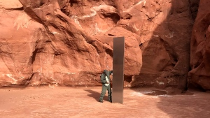 FILE - In this Nov. 18, 2020, file photo provided by the Utah Department of Public Safety, a Utah state worker stands next to a metal monolith in the ground in a remote area of red rock in Utah. The mysterious silver monolith that was placed in the Utah desert has disappeared less than 10 days after it was spotted by wildlife biologists performing a helicopter survey of bighorn sheep, federal officials and witnesses said. (Utah Department of Public Safety via AP, File)