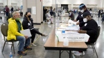 FILE - Election workers, right, verify ballots as recount observers, left, watch during a Milwaukee hand recount of presidential votes at the Wisconsin Center, Friday, Nov. 20, 2020, in Milwaukee. Wisconsin finished a partial recount of its presidential results on Sunday, Nov. 29, 2020 confirming Democrat Joe Biden's victory over President Donald Trump in the key battleground state. (AP Photo/Nam Y. Huh)